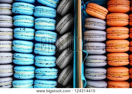 Varicolored tasty macaroons in boxes, close up