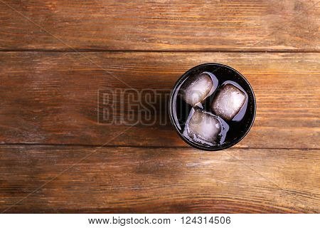 Glass of water with ice blocks  on wooden background, top view