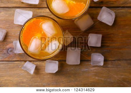 Glasses of orange juice with ice block on wooden background