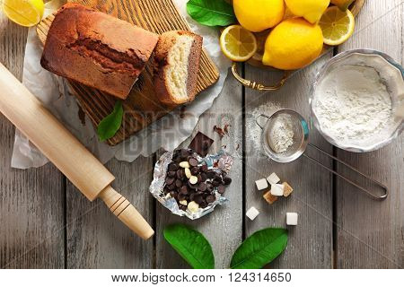 Composition of tasty cake with chocolate morsels and lemon on grey wooden background, top view