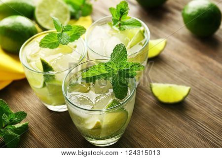 Mojito drink with lime and mint on wooden table