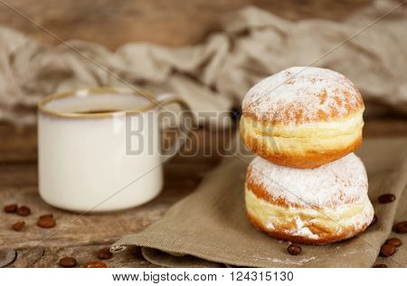 Delicious sugary donuts with cup of coffee on napkin closeup