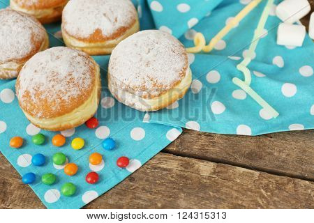 Delicious sugary donuts with blue napkin on wooden table closeup