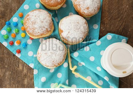Delicious sugary donuts with blue napkin on wooden table, top view