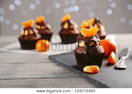 Tasty cupcakes with fruits on slate plate over light wooden background