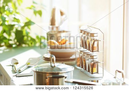 Table with utensils and spices in the kitchen beside window