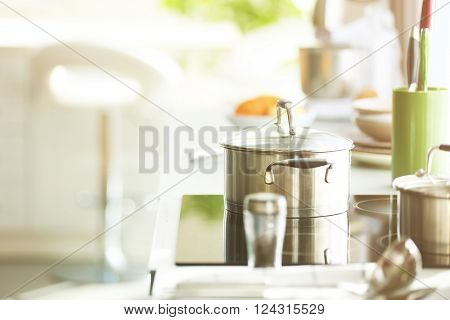 Modern electric stove with utensils and vegetables in the kitchen beside window