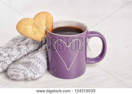 Heart shape cookie on cup of coffee on table closeup