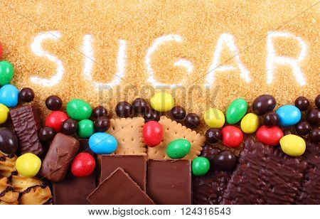 Word sugar written in granulated natural brown cane sugar and a lot of candies and cookies, concept of too many sweets and unhealthy food