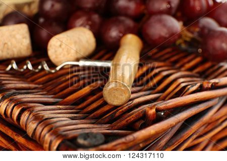 Wine corks and tailspin with bunch of grapes on wicker background