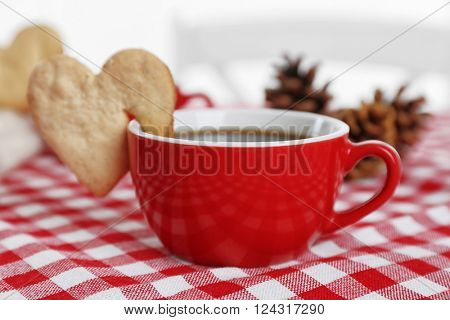 Heart shape cookie on cup of coffee on checkered napkin closeup