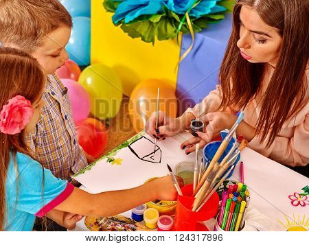 Children with teacher woman painting on paper at table  in  kindergarten . Balloons on floor.