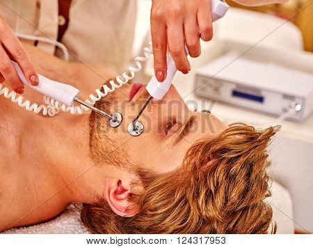 Man gets revitalizing electric facial peeling hydradermie at beauty salon.