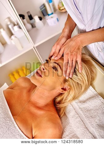 Woman middle-aged take face and neck rejuvenating massage in spa salon.