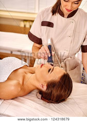 Young woman gets rejuvenating electric ultrusound facial massage at beauty salon.