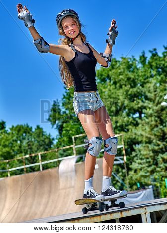 Teen girl jumping on his skateboard outdoor. Girl do  stunt aganist blue sky.