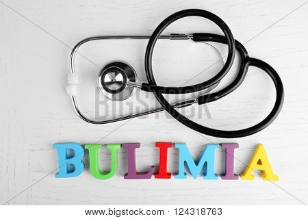 Bulimia colorful word and stethoscope on white background.