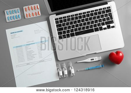 Doctor table with medicines, thermometer and laptop, top view