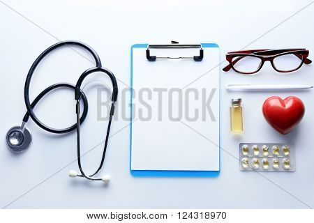 Doctor table with medicines, stethoscope and glasses, top view