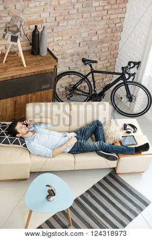 Casual young man relaxing at home, lying on sofa, talking on mobilephone.