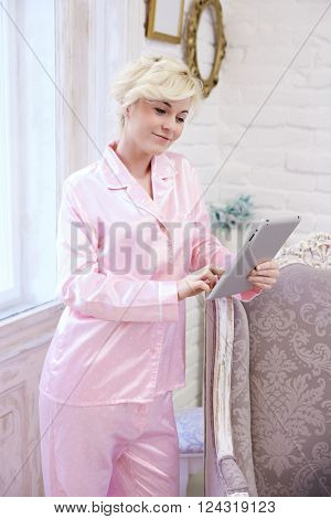Young woman in pink silk pajamas using tablet computer at stylish home.