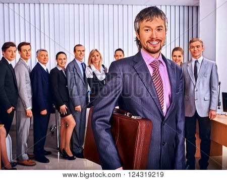 Happy group business people in office. Imposing man keeps suitcase standing in the foreground.