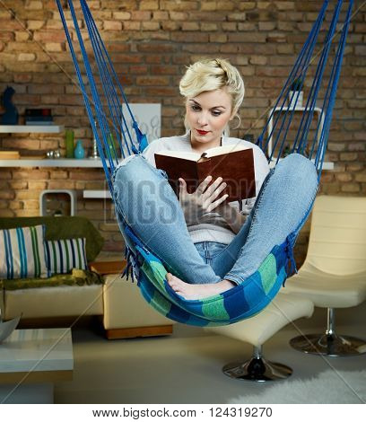 Young woman relaxing in hammock like chair at home, reading a book.