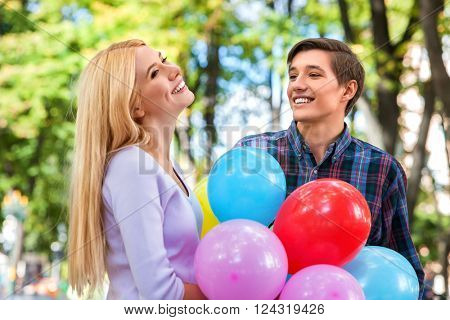 Young couple keeps balloons happy laugh and flirting in  park  and looking away.