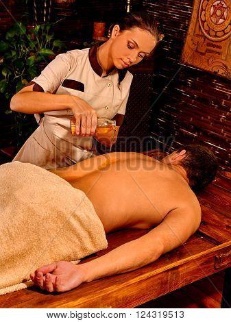 Man  having oil Ayurveda spa treatment. Asian masseuse.
