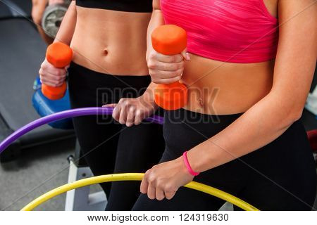 Group of female people with bare stomach working with  dumbbells and hoop his body at gym. Bare female belly .