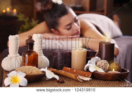 Beautiful young girl with towel lying on massage table and aromatic candles with salt in spa salon