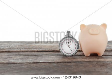 Beige piggy bank and a timer on white background