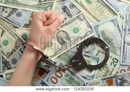 Hand in handcuffs on dollar banknotes. Corruption concept
