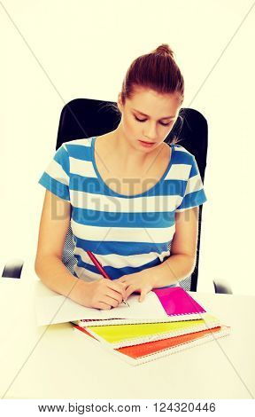 Teenage woman doing homework behind the desk