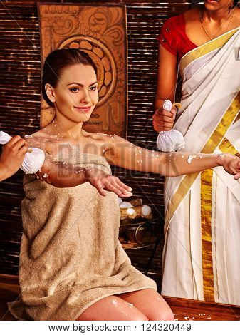 Woman with hands forward having ayurvedic massage with pouch of rice. Passage to India