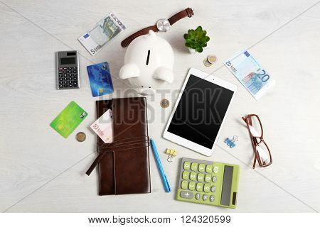 Piggy bank, office supplies and money on a white desk, top view