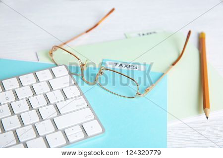 Folder with tax documents, glasses, pencil and keyboard on white wooden table
