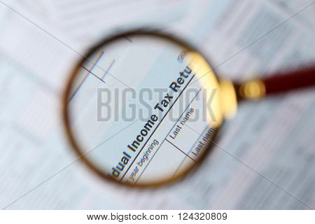 1040 Individual Income Tax Return Form  under magnifying glass, top view
