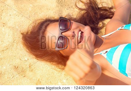 Happy Beautiful model girl in Sunglasses having fun on the Beach. Summer Vacation. Laughing female enjoying Nature, lying on sand. Attractive young Woman at the Beach. Thumb up. Sun Tanning