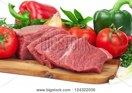closeup fresh raw beef meat slices over wooden board with vegetables on a white background
