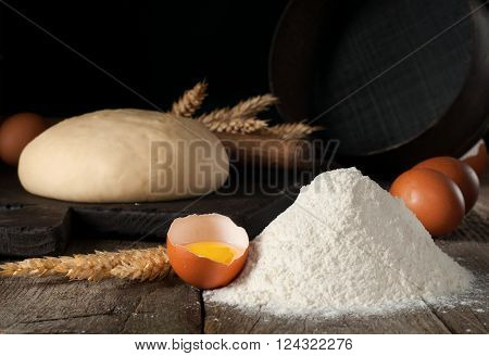 handful of wheat flour closeup with broken raw brown eggs and fresh dough rolling pin ears of wheat and sieve on a wooden table in a bakery. Bakery background