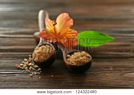 Wooden spoons with sea salt and exotic flower on wooden background