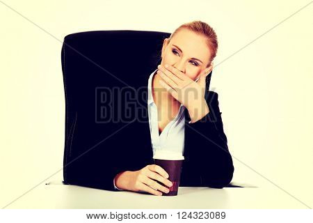 Tired business woman with coffee in paper cup behind the desk