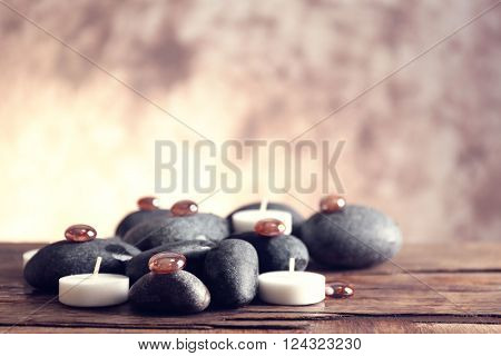 Spa still life with stones and candlelight on blurred pastel background