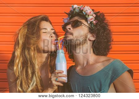 Hipster couple drinking milk from bottle, going crazy and having great time together. Terracotta urban wall background.