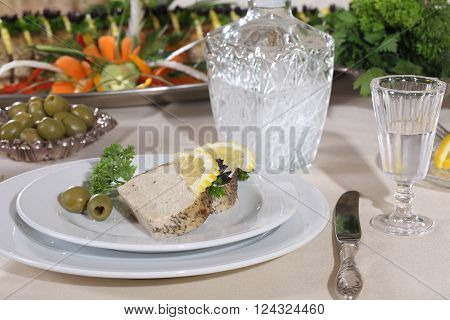 pike baked in the oven served with lemon and olives and vodka in pitcher