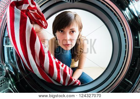 Funnygirl loading clothes to washing machine. From inside the washing machine view