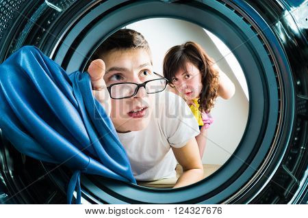 Funny couple loading clothes to washing machine. From inside the washing machine view