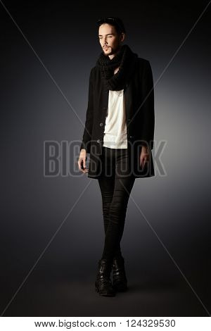 Fashion shot of a handsome male model in black suit posing over gray background. Men's beauty.