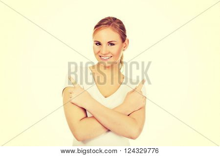 Confused young woman pointing in two different directions